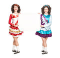 Two young women in irish dance dresses with empty paper and wigs Royalty Free Stock Image