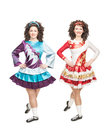 Two young women in irish dance dresses posing isolated and wigs Royalty Free Stock Image