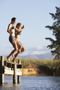 Two Young Women Jumping From Jetty Into Lake Royalty Free Stock Photo