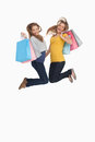 Two young women jumping with shopping bags Royalty Free Stock Photo
