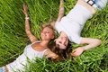 Two young women lay on green grass outdoors Stock Photo