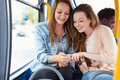 Two young women listening to music on bus wearing headphones smiling Stock Photos