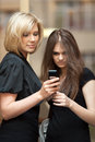 Two young women looking at a cell phone Royalty Free Stock Photo