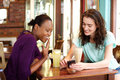 Two young women looking at mobile phone at cafe Royalty Free Stock Photo