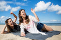 Two young women lying on beach waving and laughing Royalty Free Stock Photo