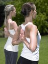 Two young women practicing yoga outside Royalty Free Stock Photography