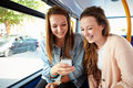 Two young women reading text message on bus whilst sitting seat laughing Stock Image