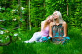 Two young women relaxing in the park Stock Images