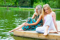 Two young women relaxing in the park near the pond Royalty Free Stock Image