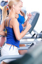 Two young women run on machine in the gym Stock Images