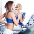 Two young women run on machine in the gym Royalty Free Stock Photos