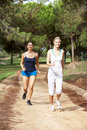 Two young women running in park Royalty Free Stock Photo