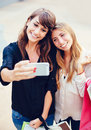 Two young women shopping at the mall taking a Royalty Free Stock Photography