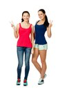 Two young women sitting and showing victory sign smiling Royalty Free Stock Photo