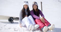 Two young women sitting waiting in the snow Royalty Free Stock Photo