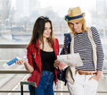 Two young women stand with a suitcase at the railway station or the airport. Look at the card and passport. Royalty Free Stock Photo