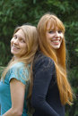 Two Young Women standing back to back Royalty Free Stock Photos