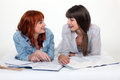 Two young women studying at a desk Stock Images