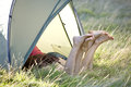 Two young women with their legs sticking out of a tent Royalty Free Stock Photo