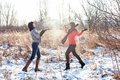 Two young women throwing snow female friends walking in park in winter and Stock Image