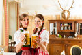 Two young women in traditional bavarian tracht in restaurant or pub with beer and beer stein Royalty Free Stock Images