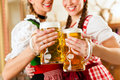 Two young women in traditional bavarian tracht in restaurant or pub with beer and beer stein Stock Image
