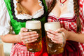 Two young women in traditional bavarian tracht in restaurant or pub with beer and beer stein Royalty Free Stock Image