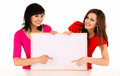 Two young women with whiteboard white background Royalty Free Stock Photos