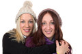 Two young women in winter clothing hug each other isolated on a white background Stock Photos
