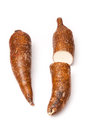 Two yuca roots one cut to show the white flesh of this vegetable and both of which here have unblemished brown skins white Stock Photo
