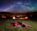 Twosome admiring the bright stars and lying on the grass Royalty Free Stock Photo