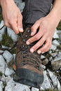 Tying the hiking boots of a hiker on a rock in mountains Royalty Free Stock Image