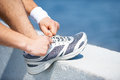 Tying shoelaces close up of man on sports shoe while standing outdoors Stock Photo