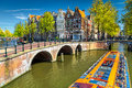 Typical Amsterdam canals with bridges and colorful boat, Netherlands, Europe Royalty Free Stock Photo
