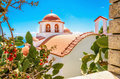 Typical greek church with red roofing greece cozy view on plants and stone wall on island Royalty Free Stock Image