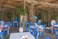 A typical greek taverna with white and blue tables chairs and objects Stock Photos