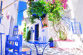 Typical greek traditional village in summer with white walls blue furniture and colorful bougainvilla skiathos island greece e old Royalty Free Stock Photography