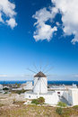 Typical greek windmill on santorini against blue sky with clouds cyclades islands greece Royalty Free Stock Image
