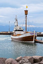 Typical iceland harbor with wooden ship at overcast day vertical shot Royalty Free Stock Image