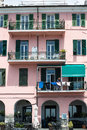 Typical italian facade imperia italy may with bar in the basement and several floors with balconies above a woman is hanging out Stock Image