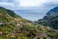 Typical landscape of Madeira island, serpentine mountain road, houses on the hills and ocean view Royalty Free Stock Photo