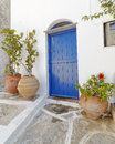 Typical mediterranean island house facade blue door and flowerpots Stock Image
