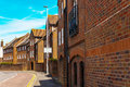 Typical old English buildings, low brick buildings across a narr
