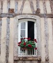 Typical old wall with wood beams in France and window with flower pots