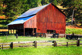 Typical rustic old working barn a with common vertical lap board siding details with rail fencing corrals in Stock Photography