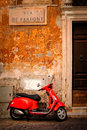 Typical scene with a red scooter on a narrow central Rome street Royalty Free Stock Photo
