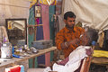 Typical small india barber shop in tent along the street nagaur circa february focus on and his client still with Royalty Free Stock Images