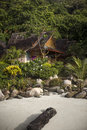 Typical thai bungalow in front of a beach surrounded by a tropical greenery Royalty Free Stock Photo