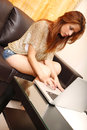 Typing on a laptop young adult woman while sitting the sofa Royalty Free Stock Photography