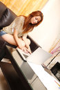 Typing on a laptop young adult woman while sitting the sofa Royalty Free Stock Images